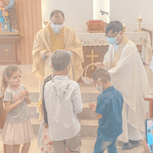 children_receiving_gifts_from_priests